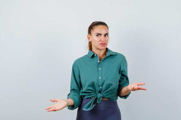 Молодая красивая женщина в зеленой рубашке, вопросительно протягивая руки, глядя в сторону и задумчиво, вид спереди.