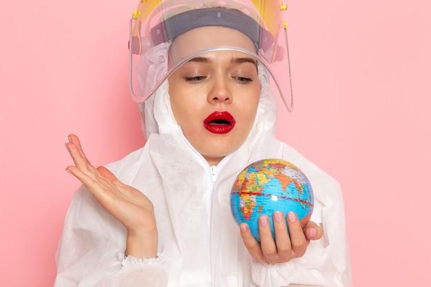 Молодая красивая женщина в специальном белом костюме и желтом шлеме держит маленький глобус на розовом