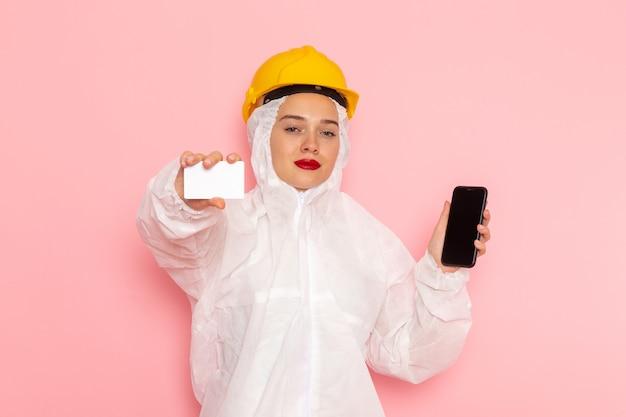 特別な白いスーツとピンクの電話とカードを保持している黄色いヘルメットの若い美しい女性