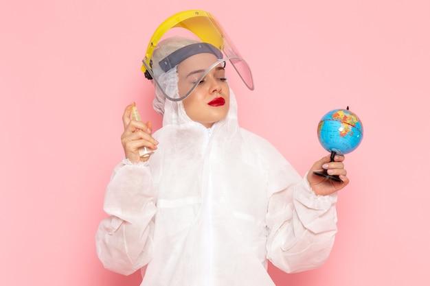 Молодая красивая женщина в специальном белом костюме, держащая спрей и глобус на розовом