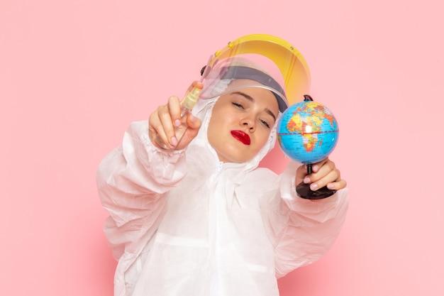 Молодая красивая женщина в специальном белом костюме, держащая спрей и маленький глобус на розовом