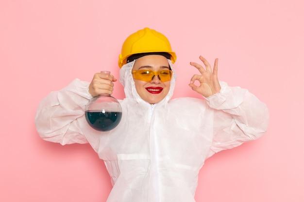 ピンクに青いソリューションを保持している保護用のヘルメットを身に着けている特別な白いスーツの若い美しい女性
