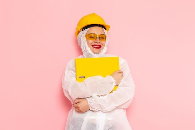 Молодая красивая женщина в специальном белом костюме в защитном шлеме держит файлы на розовом