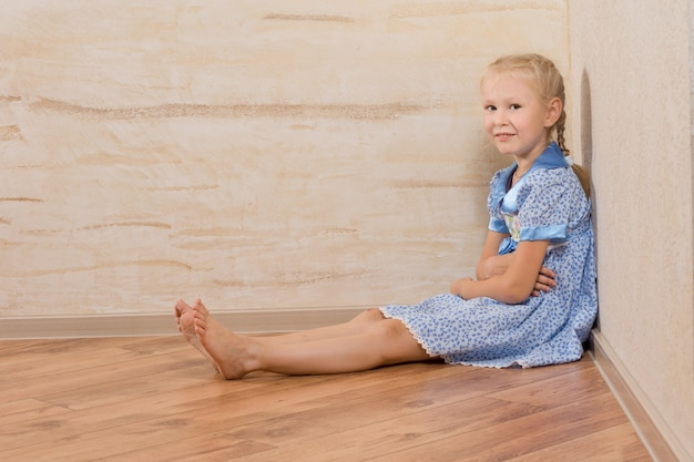 Молодая красивая женщина в белом и синем платье, сидя на полу. изолированные на деревянных стенках