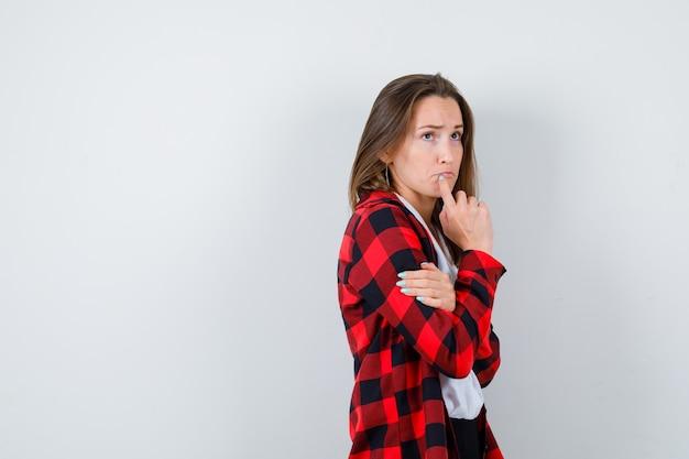 턱에 손가락을 대고 있는 젊고 아름다운 여성은 캐주얼 복장을 하고 화난 표정을 짓고 있습니다.