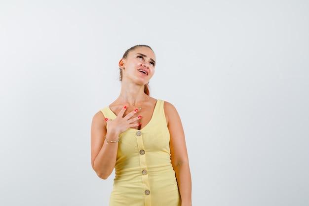 Giovane bella femmina che tiene la mano sul petto mentre osserva in su in vestito e sembra infastidito. vista frontale.