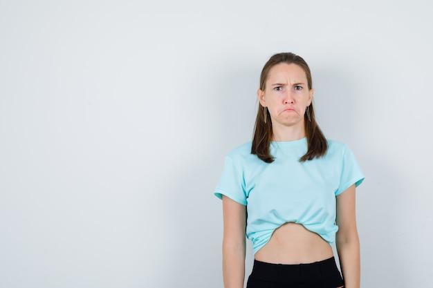 젊은 아름다운 여성이 티셔츠를 입은 카메라를 보고 심술궂은 모습을 하고 있습니다.