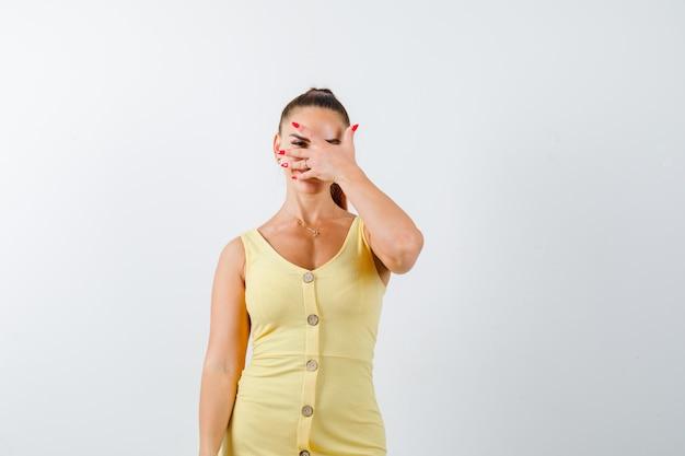 ドレスを着た指を通して見て困惑している若い美しい女性。正面図。