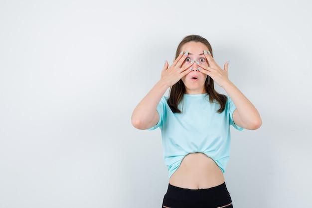 Tシャツを着て指をのぞき、好奇心旺盛な正面図を見る若い美しい女性。