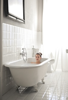 Young beautiful female lying in a bathtub and having a rest