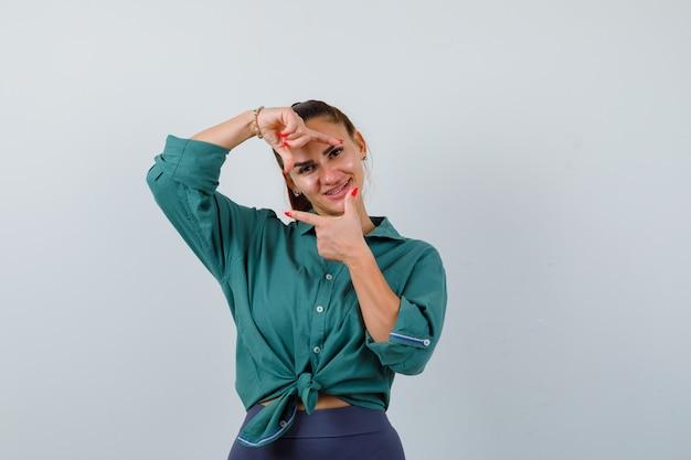 Giovane bella donna che fa gesto di cornice in camicia verde e sembra beata. vista frontale.
