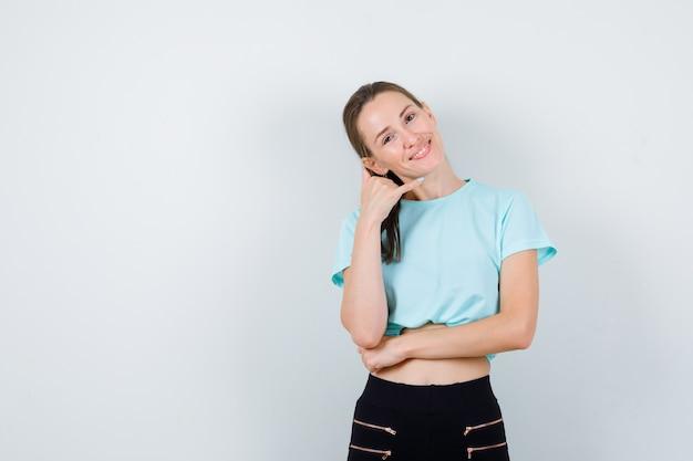 Молодая красивая женщина делает телефонный жест в футболке, штанах и выглядит веселым. передний план.