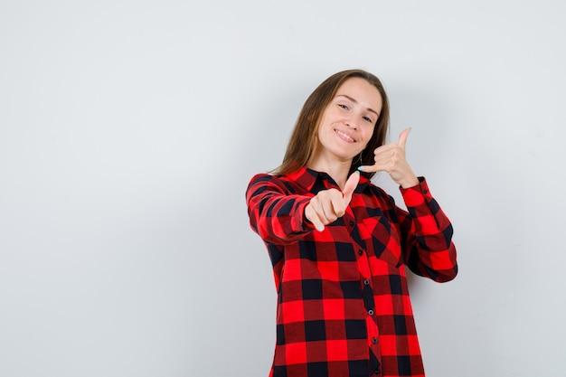 Молодая красивая женщина делает телефонный жест, указывая на верхний правый угол в повседневной рубашке и выглядит блаженным. передний план.
