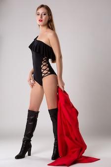 黒のセクシーなボディースーツと明るい赤いレインコート、ファッションポートレートを保持しているハイヒールのブーツでポーズをとる若い美しい女性モデル