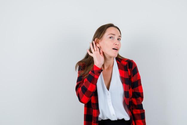 Giovane bella femmina che ascolta il segreto in abbigliamento casual e sembra concentrata. vista frontale.