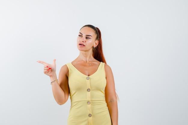 Молодая красивая женщина указывая налево в платье и глядя расстроенным. передний план.