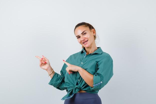 緑のシャツを着て左を指して陽気に見える若い美しい女性。正面図。