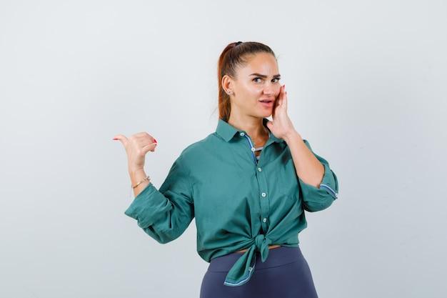 녹색 셔츠에 입 근처에 손을 유지하고 호기심, 전면보기 찾고있는 동안 엄지 손가락으로 왼쪽을 가리키는 젊은 아름다운 여성.