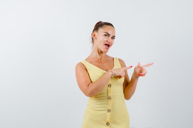 Giovane bella femmina che indica a destra in vestito e che sembra allegra, vista frontale.