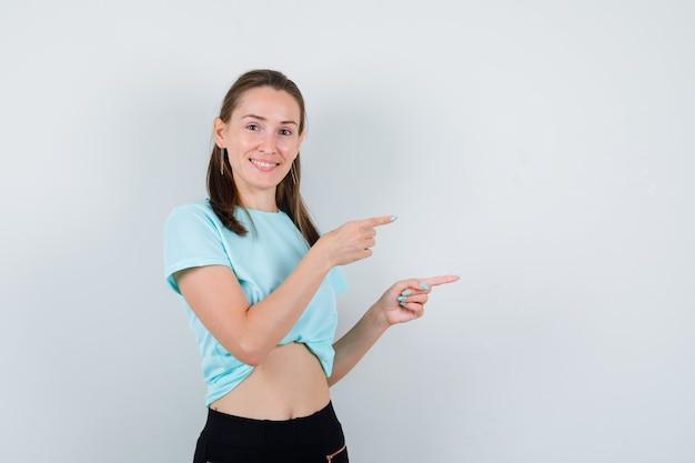 Giovane bella donna che punta a destra in maglietta e sembra allegra, vista frontale.