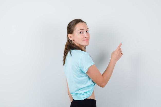 Giovane bella donna che punta all'angolo in alto a destra in t-shirt e sembra allegra.