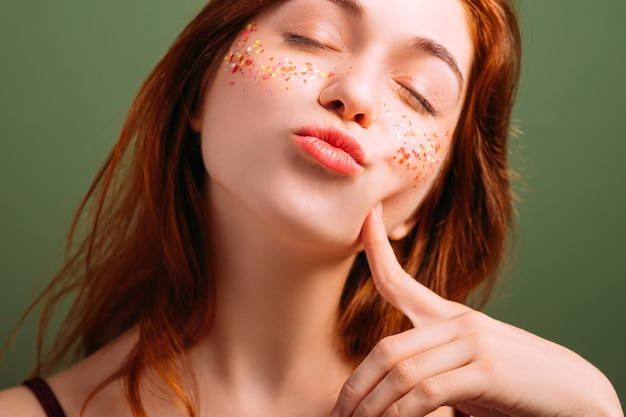 Young beautiful female portrait. woman self esteem. pout lips blowing kiss. finger at cheek. closed eyes.