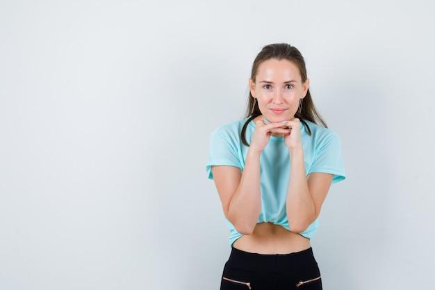 Tシャツの指で顔の肌に触れて自信を持ってポーズをとる若い美しい女性。正面図。