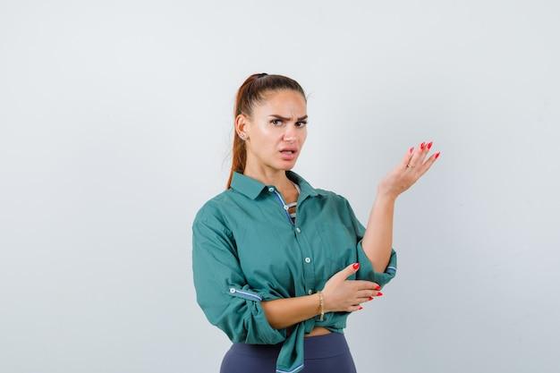 젊고 아름다운 여성이 녹색 셔츠를 입고 화를 내며 정면을 바라보며 손을 들고 있습니다.