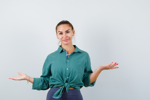 Молодая красивая женщина показывает беспомощный жест в зеленой рубашке и выглядит смущенным. передний план.