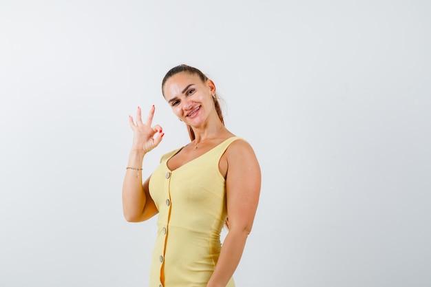 Молодая красивая женщина показывает хорошо жест в платье и выглядит весело. передний план.