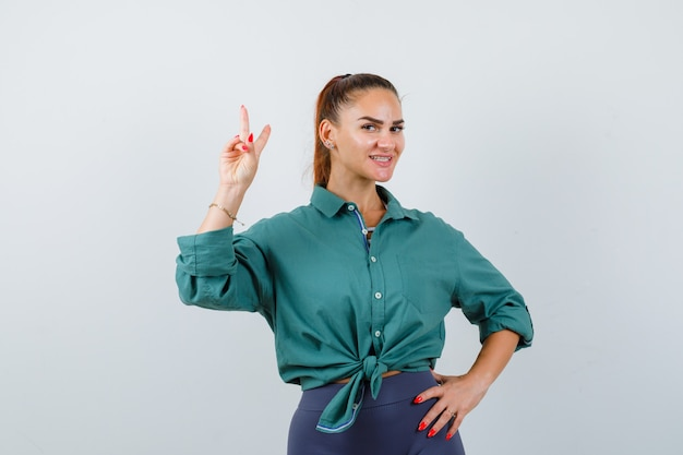 Молодая красивая женщина показывает жест мира в зеленой рубашке и выглядит позитивно, вид спереди.