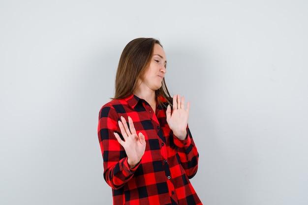 若い美しい女性は、ジェスチャーを拒否し、カジュアルなシャツを着て脇を見て、不満を見て、正面図。