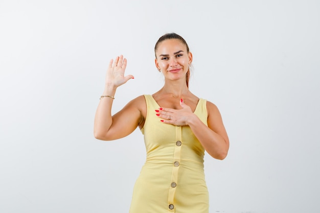 Giovane bella femmina che mostra il palmo della mano mentre tiene la mano sul petto in abito e sembra beata. vista frontale.