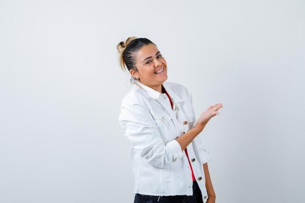 Tシャツ、白いジャケットで歓迎のジェスチャーを示し、喜びに見える若い美しい女性。正面図。
