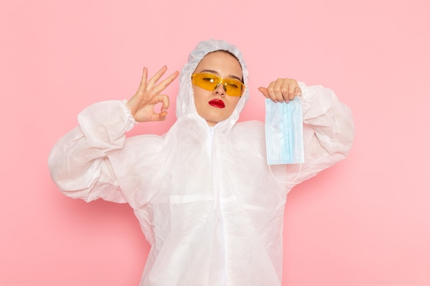 Young beautiful female in special white suit holding sterile protective mask on pink