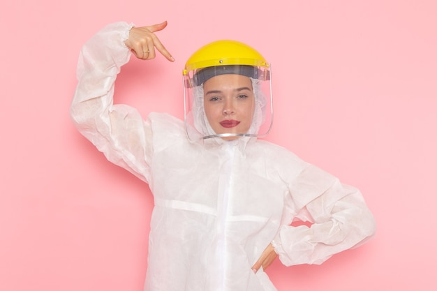 Young beautiful female in special white suit and yellow helmet posing on pink