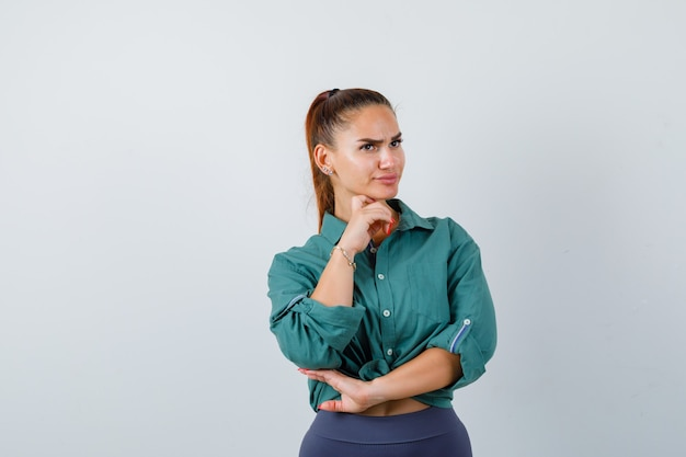 Young beautiful female standing in thinking pose in green shirt and looking puzzled. front view.
