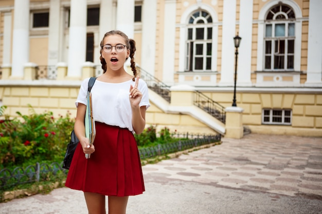 Young beautiful female student in glasses holding folders, thinking outdoors.