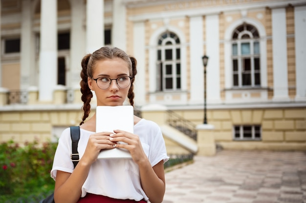 Young beautiful female student in glasses holding tablet, thinking outdoors.