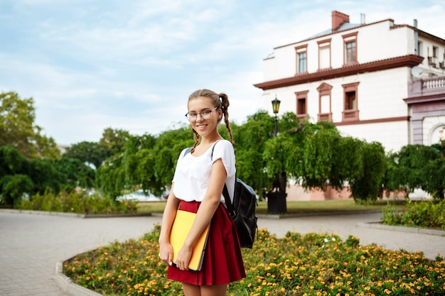 Young beautiful female student in glasses smiling, holding folders outdoors, park surface