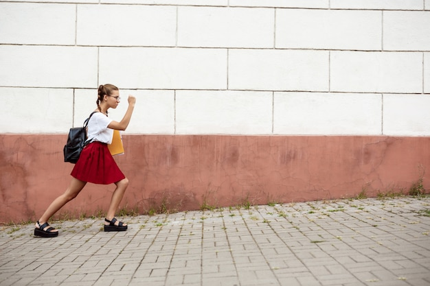 Молодая красивая студентка в очках шел по улице, держа папки