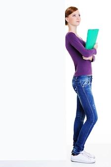 La giovane bella studentessa con tranquilla emozione sul viso in piedi vicino al cartellone vuoto