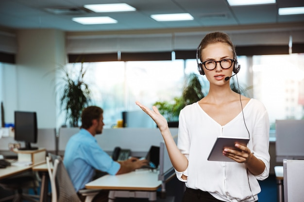 Young beautiful female support phone operator speaking, consulting, over office
