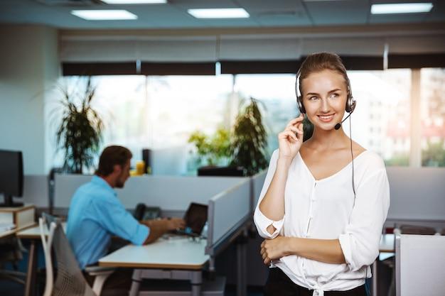 Giovane bello operatore telefonico femminile di sostegno che parla, consultando, sopra l'ufficio