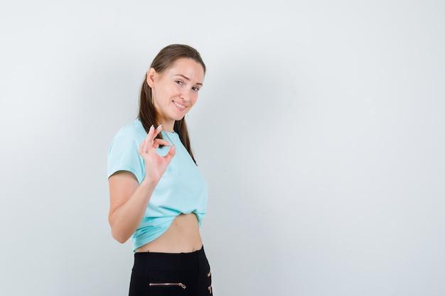 Giovane bella donna in t-shirt, pantaloni che mostrano gesto ok e sembrano beati, vista frontale.