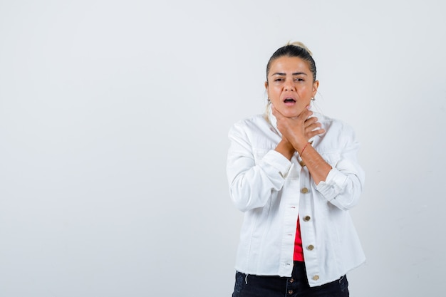 Young beautiful female in t-shirt, white jacket making suicide gesture and looking annoyed , front view.