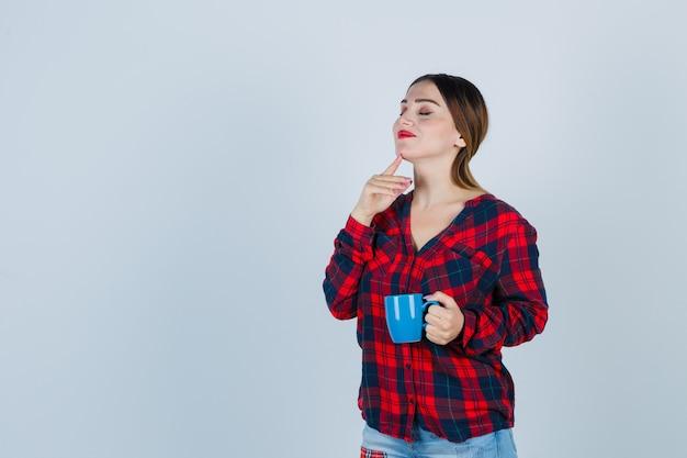 カジュアルなシャツ、ジーンズ、陽気にカップを保持しながら指で顎に触れる若い美しい女性。正面図。