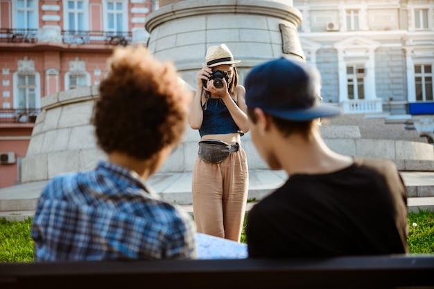 Young beautiful female tourist taking picture of her friends.