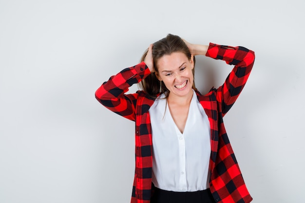 Giovane bella donna che cerca di sistemare i capelli in un abbigliamento casual e sembra infastidita, vista frontale.