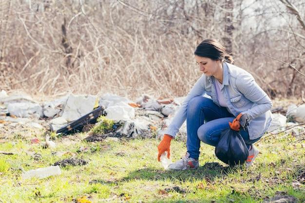 젊은 아름다운 여성 자원 봉사자가 숲에서 플라스틱 쓰레기를 수집합니다